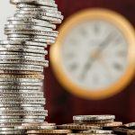 zegarek i wieża z monet, z tyłu zegarek - symbol kredytu