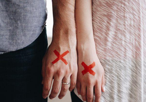 dłonie mężczyzny i kobiety, na każdej z nich namalowany czerwony krzyżyk - symbol rozwodu