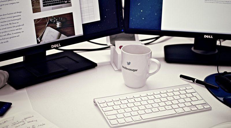 Komputer z wynajmu komputerów składający się z dwóch monitorów i klawiatury stojących na stole razm z kubkiem